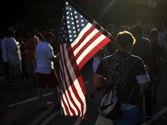 A young man walks with an American Flag at an Independence Day celebration