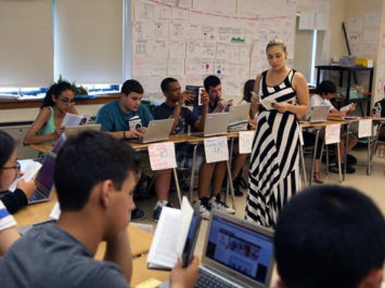 """Suzanne D'Arco, a 10th grade English teacher at Tuckahoe High School, reads """"Twelve Angry Men"""" with her class."""