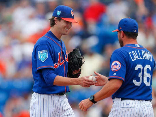 Mets starting pitcher Jacob deGrom hands the ball to