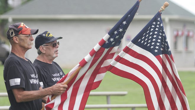 U.S. Veterans Harry Richardson and Neil Minor carry the flags at Freedom Fest in Westmoreland, TN on Saturday June 23, 2018.