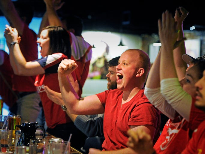 John Hunt, center, and the rest of the Arsenal Fans cheer as their team scores against Liverpool. English Football fans line the bar as games from London are piped into the Fleet Street Pub in Printers Alley. Sunday Feb. 16, 2014, in Nashville, TN.