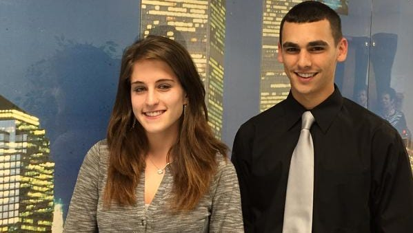 Carly Hochron and Ryan Bakutes, seniors at North Rockland High School, pose at the Academy of Finance office at the school, in front of a mural of Manhattan's financial district.