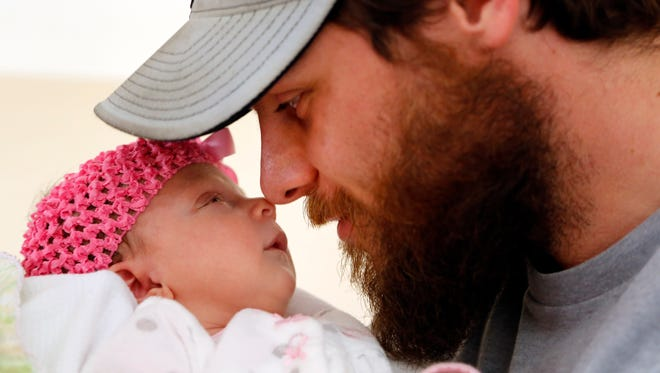Nate Yoho of Grimes nuzzles his infant daughter Caralyn, who was born Nov. 26 after being carried by a surrogate mother, Kara Stetson.  Nate's wife, Laura, died of brain cancer before Caralyn was born.