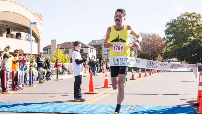 The first half marathoner crosses the finish line during the Run For The Schools in downtown Iowa City. October 18, 2015. Zak Neumann freelance for the Press Citizen.