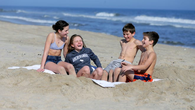 Avery Schneider, 12, Emily Thompson, 12, Jack Thompson, 10, and Nathaniel Schneider, 10, all of Basking Ridge enjoy the day's 64 degree temperature on the beach in Asbury Park on Tuesday Feb. 20.