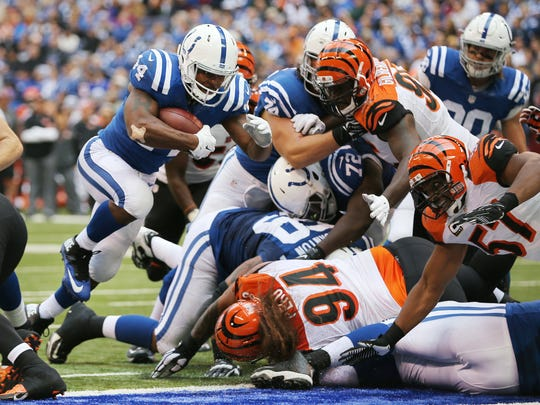 Indianapolis Colts running back Ahmad Bradshaw blasts into the end zone through the Bengals defense for a touchdown in the first half of Sunday's game at Lucas Oil Stadium on October 19, 2014.