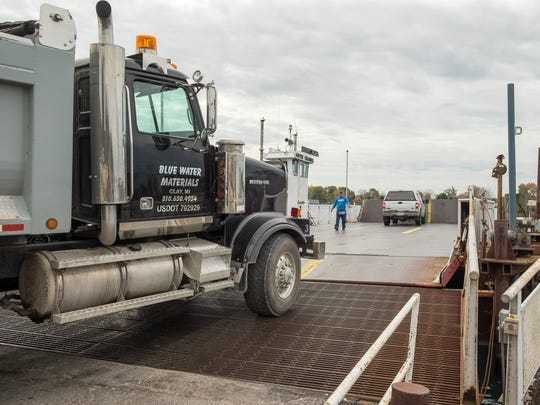 Vehicles are guided onto Champion's Auto Ferry in Clay