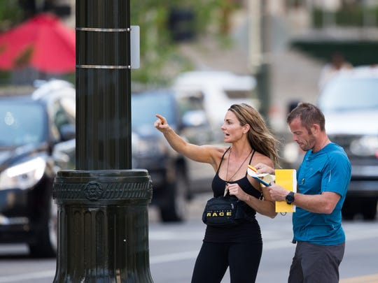 "Two ""Amazing Race"" contestants interpret clues on Larned Street in Detroit while filming the 31st season of The Amazing Race on Tuesday, July 3, 2018."