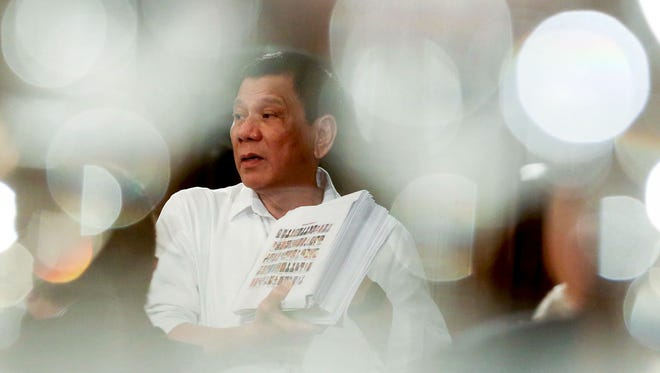 This handout photo taken on Dec. 12, 2016 and released by the Presidential Photographers Division (PPD) shows Philippine President Rodrigo Duterte showing a list of police, and government officials involved in illegal drugs during a forum with local and foreign businessmen at Malacanang Palace in Manila.