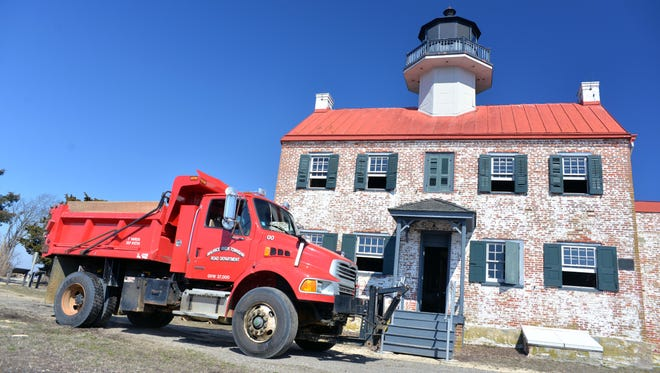 A road department truck delivers donated sand to create a temporary berm at East Point Lighthouse in March. New renovations are scheduled to start at the lighthouse in June.