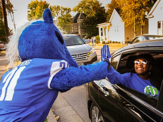 Lightning, MTSU's mascot, high fives a fan in the Homecoming