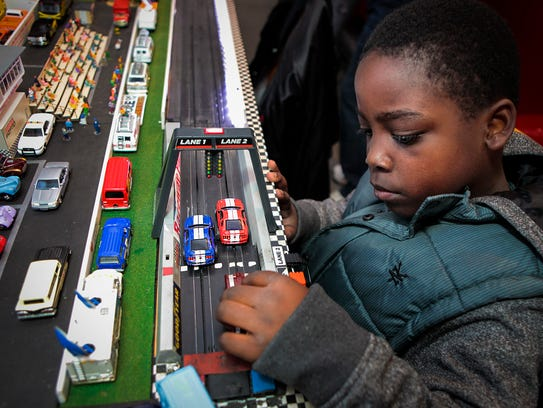 Elijah Burchell plays with his grandfather's miniature