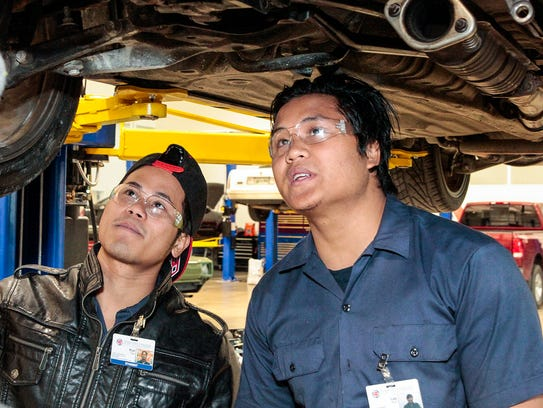 Kue Say, left, and Lay Htoo look underneath an automobile