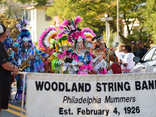 The Mummers' Woodland String Band entertains the crowd on Broad Street at the the Middletown Peach Festival.