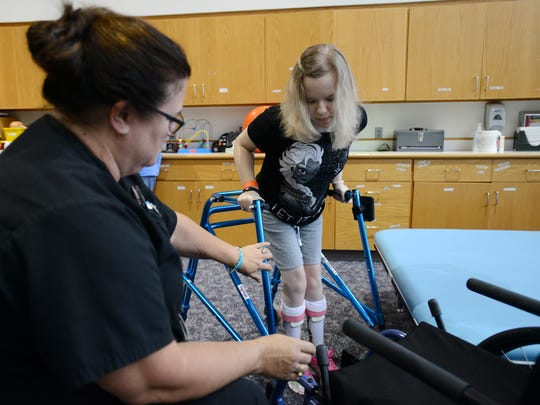 Logan Hopper works with Laura Peace, a senior occupational therapist at Shriners Hospitals for Children, on Tuesday.