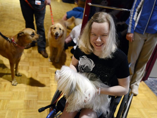 Logan Hopper takes a break from occupational therapy to pet therapy dogs visiting Shriners Hospitals for Children on Tuesday..
