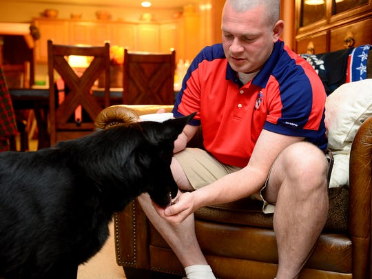 Johnnie Trout hand feeds his service dog Raven Friday,