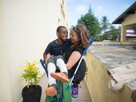 Katie Keegan holds one of the boys who had his legs repaired at Mercy Ships.