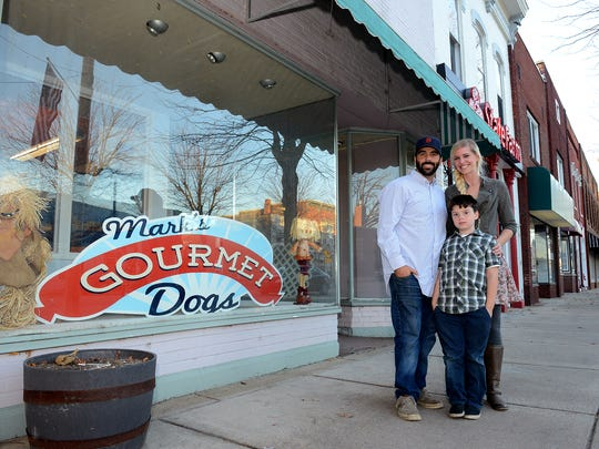 Mark and Krysta McGee, owners of Mark's Dogs, along with their son Christian, 7, stand outside their new restaurant space in Eaton Rapids, Tuesday, November 3, 2015.