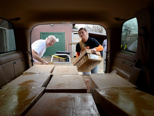 Tom Cullimore, left, and Hellanna Webster, with Specialized Deer Processing, load up Cullimore's vehicle with meat that he'll later deliver to the Clinton County and Williamston food banks. Cullimore runs an initiative called HOPE - Help Other People Eat - and picks up food from meat processors and delivers it to food banks.