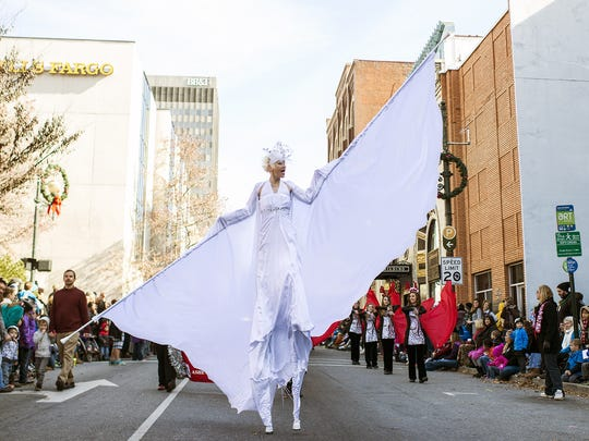 A stilt walker performs during the 2014 Asheville Holiday Parade in downtown, Saturday, Nov. 22. Thousands attended the parade to watch the nearly 100 performances, floats and marches taking over Biltmore and Patton avenues.