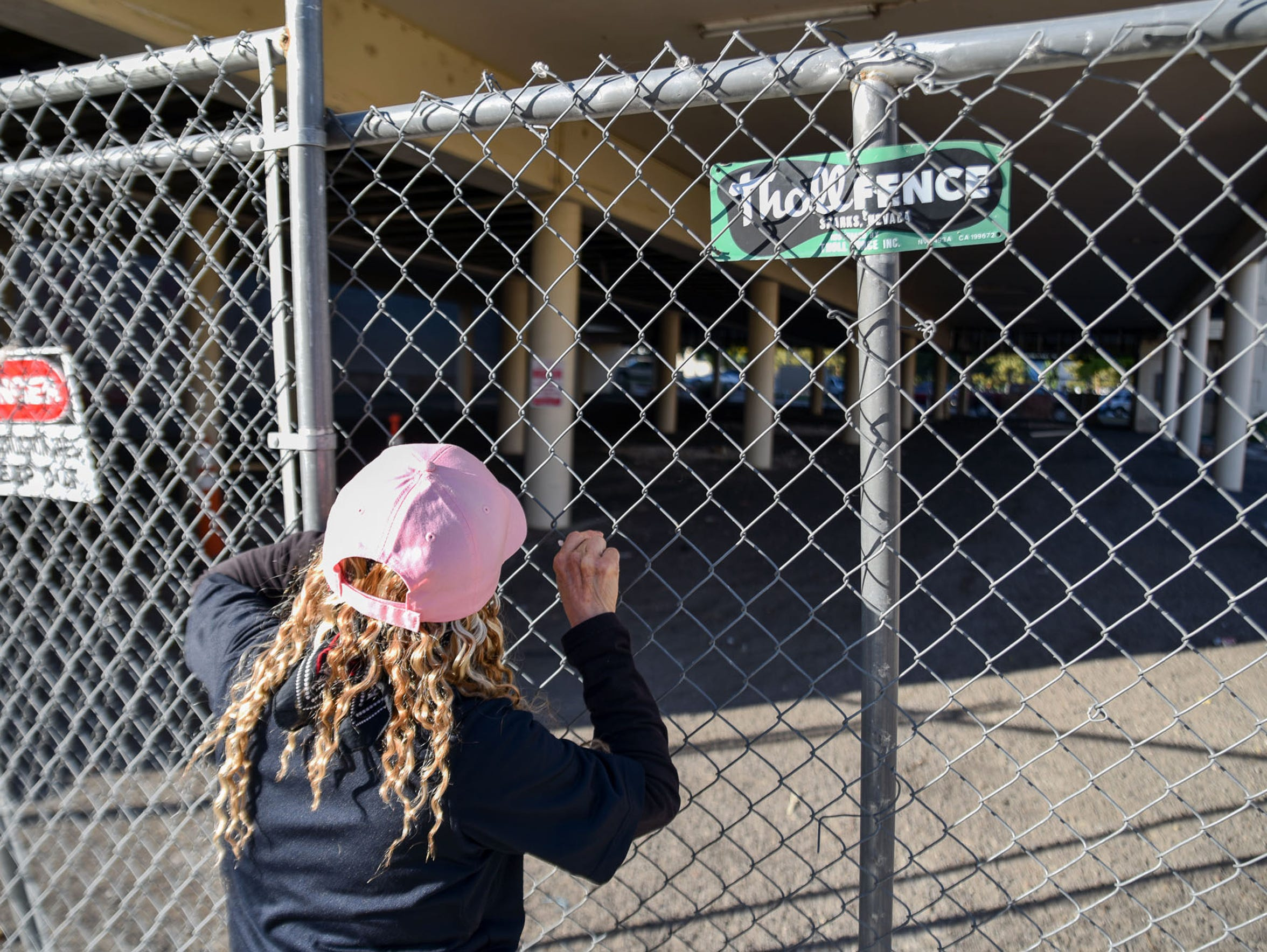 Cindi Gil-Blanco peers through the fences of the vacant