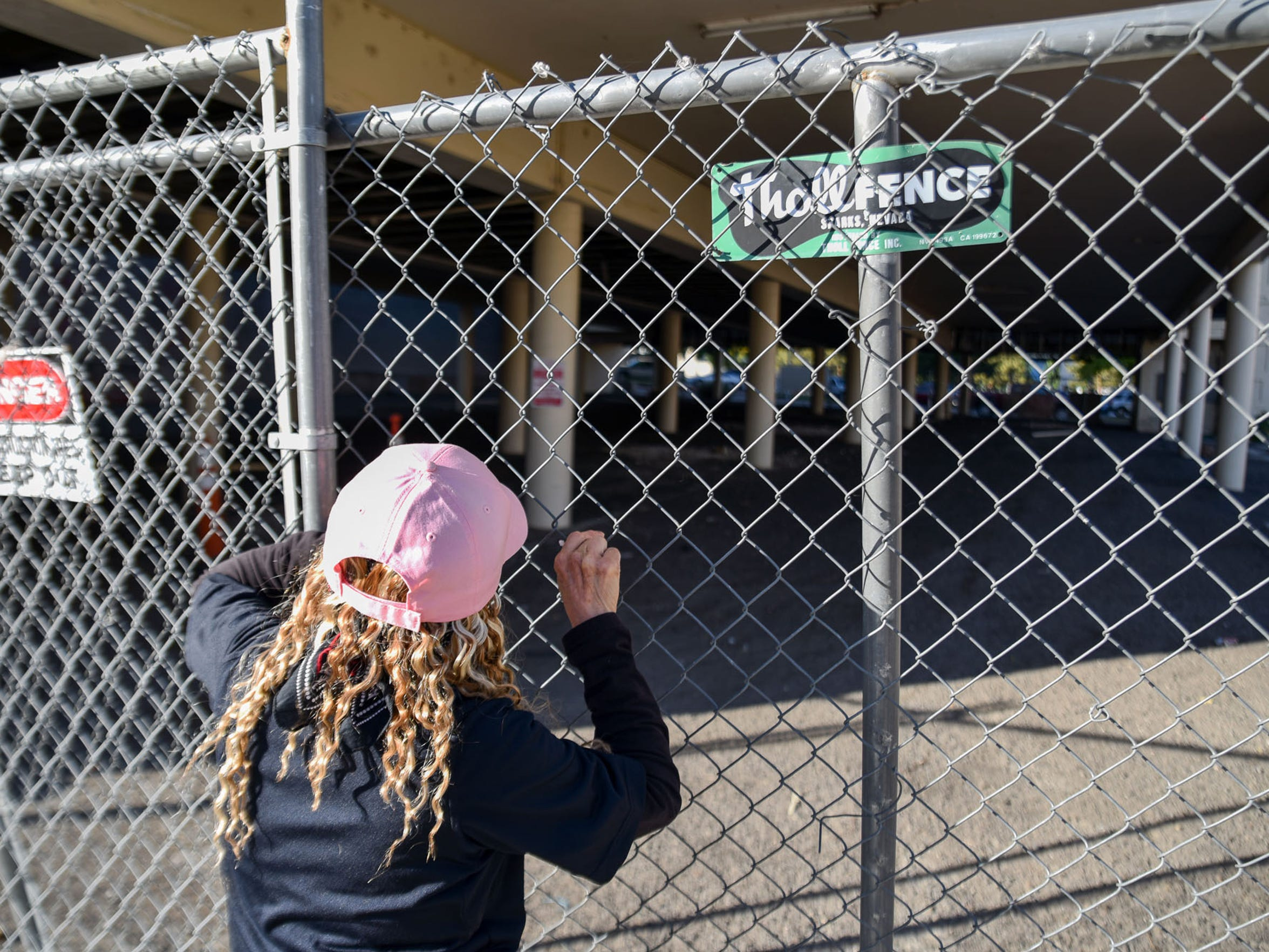 Cindi Gil-Blanco peers through the fences of the vacant Center Lodge to take stock of the violations within. This building is on her top list of blighted properties.