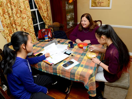 Lansing State Journal Michigander reporter Kathleen Lavey sits with her daughters Julianna, 15, right, and Ella, 13, after school Thursday, November 20, 2015 at their home in East Lansing. Lavey adopted Juliana from China 15 years ago this Thanksgiving. She adopted Ella from China two years later.