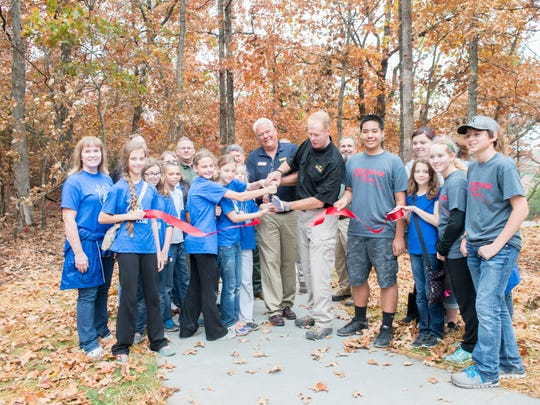 A group of young people join Bill Bryan, Director of Missouri State Parks, in officially dedicating the 1000th Mile Trail.