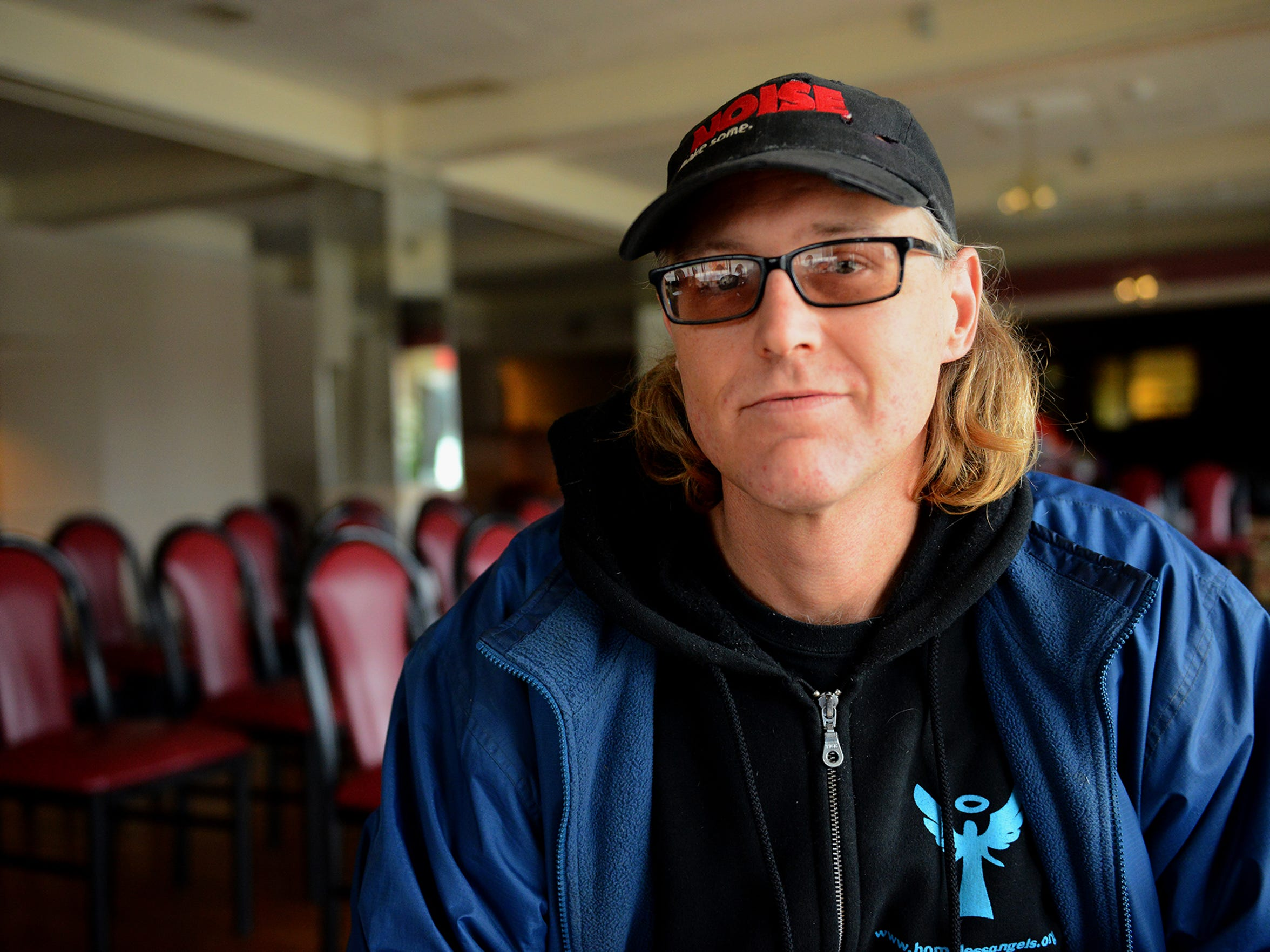 """Michael """"Cookie"""" Johns sits for a photograph at the Magnuson Hotel in south Lansing Wednesday, Dec. 16. Johns has been homeless for the last 20 years he now does maintenance and work around the hotel while staying there through the non-profit Homeless Angels."""
