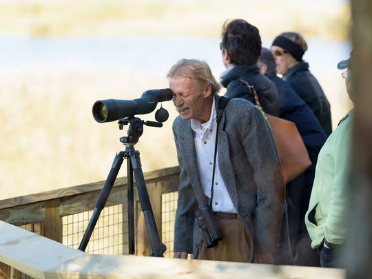 Bill Stewart, President, Delmarva Ornithological Society peers through a spotting scope on the the wildlife viewing platform at Thousand Acre Marsh.