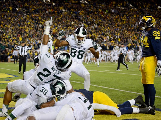 Spartans Khari Willis (27), Monty Madaris (88)  and others celebrate in the endzone as Michigan players look on after Jalen Watts-Jackson scored the winning touchdown after time expired to beat the Wolverines 27-23 Saturday, October 17, 2015, at Michigan Stadium in Ann Arbor.
