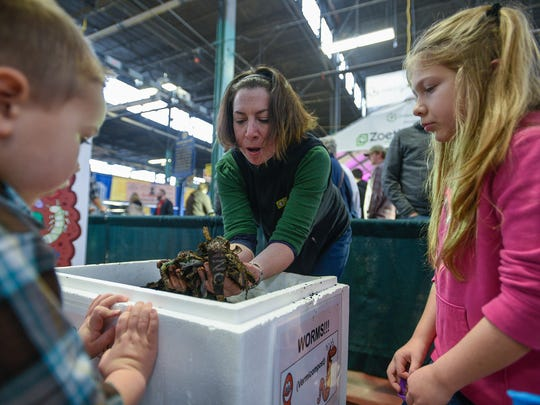 Weston Young, left, and sister Lydia Young watch Maggie Saska dig into mixed compose that has worms in it at the 100th Pennsylvania Farm Show in Harrisburg, Pa. on Saturday Jan. 9, 2015. The display was part of Know Your Farmer.