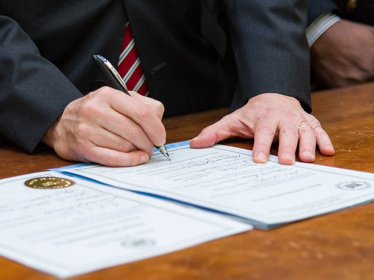 Gov. Jack Markell signing House Joint Resolution 10, proclamation of resolution apologizing for Delaware's role in slavery, at the Delaware Public Archives in Dover on Wednesday morning.
