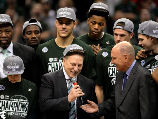 Michigan State coach Tom Izzo smiles as Big Ten commissioner Jim Delany hands him the microphone after the Big Ten tournament championship game on March 13, 2016 at Bankers Life Fieldhouse in Indianapolis.