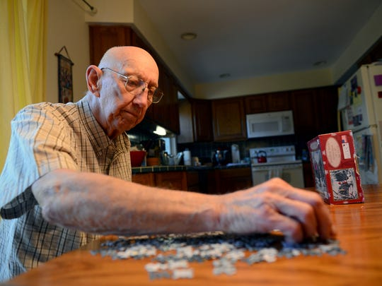 "Bob Flory puts together a puzzle, one of his favorite activities, at his home Monday, May 23, 2016, in Holt. Flory, 84, is a Korean War veteran and recently received a Purple Heart he thought was stolen along with a Bronze Star and other medals he didn't know he qualified for. Even though he was injured in battle, he said he ""didn't give a rip"" for the medals and that there were others who sacrificed more than he did."