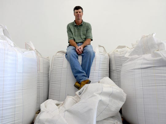 Mitten State Malts owner Larry Judge sits atop 1,600-pound sacks of barley and wheat in his warehouse Wednesday, June 21, 2016 in Okemos. Judge is starting this business and wants to use a 100-year-old strain of Spartan Barley created at MSU in 1916. The barely was popular in the 1950s but disappeared by the 1980s.