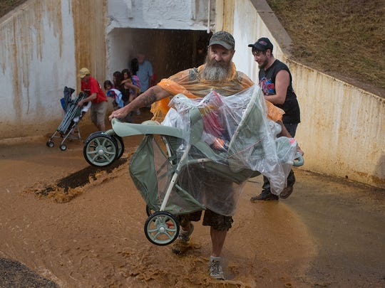 Mark Middleton of Wellsville carries a baby through the flood inside the underpass at Williams Grove Speedway.   The first race for PA Sprint Car Speedweek was rained out after the hot laps June 24, 2016.
