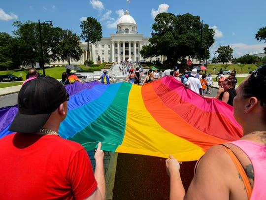 People carry the Pride flag to the Capitol during the