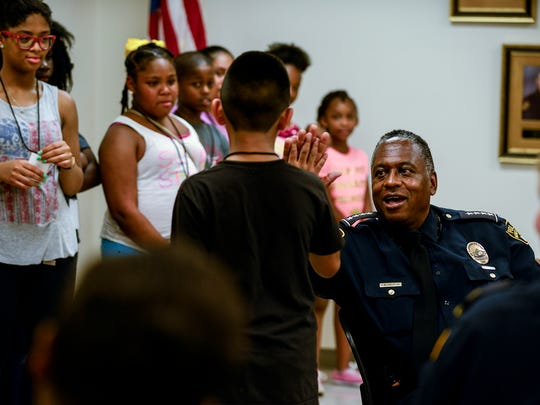 Chief Ernest Finley gives a child a high-five during a tour of the Montgomery Police Department on Tuesday, Jun. 28, 2016 in Montgomery, Ala. The tour was part of the department's Junior Police Academy, a five-day program that educates children about law enforcement.