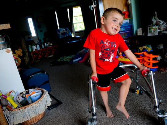 Carl Cole, 5, uses a rolling walker to get around his house July 22, 2016 in Grand Ledge. Cole lives with his grandmother Leona Simon, 66, who is his full-time caregiver. Simon drives Carl to school in Ionia and to doctor and therapy appointments in Ann Arbor, Grand Rapids, Lansing and Brighton. Her van, with nearly 300,000 miles, broke down. She cannot afford a new vehicle so she's turning to an online fundraiser for help.