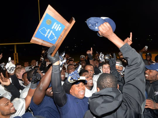 Timber Creek Regional High School football coach Rob Hinson (holding trophy) celebrates with his Chargers after their 28-24 win over Shawnee in the South Jersey Group 4 final last year.