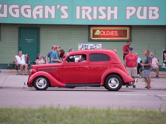 A custom hot rod is parked in front of Duggan's Irish