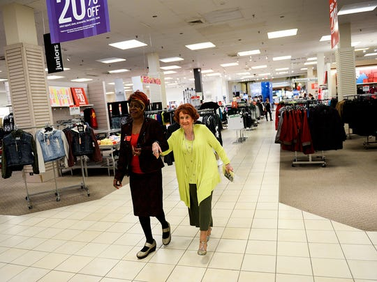 Denise Moody-Smith and Betty Collette walk through the main floor of the J.C. Penney store in the Lansing Mall store as they head to her retirement party Friday, Sept. 30, 2016. Collette, 91, is retiring from J.C. Penney after 67 years with the company.