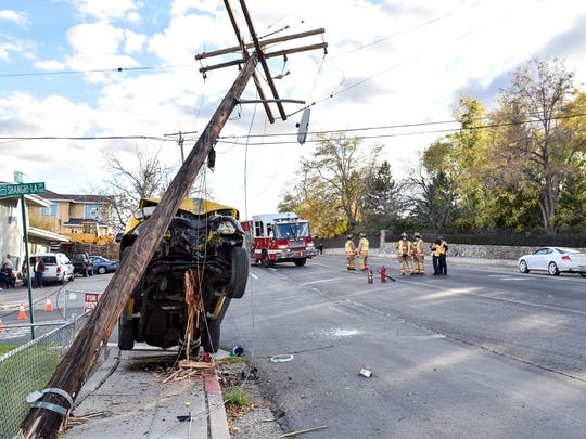 A driver of a yellow SUV drove into a power pole on Arlington Avenue and Shangri-La Drive the afternoon of Nov. 1, 2016. Police report that he was distracted. He declined to give his name. Reno firefighters were standing by in case the car or power poles fell.