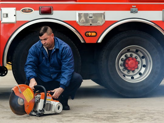Lansing firefighter Mike Potter checks to make sure the saws are running properly as he and other firefighters perform daily, routine maintenance on their fire engine and ambulance at Fire Station 1 on Friday, Nov. 11, 2016, in Lansing.  The Legislature is discussing reforms to municipal retirement systems, like the one Lansing firefighters have.