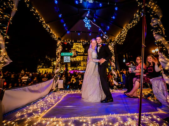 A bride and groom ride the David's Bridal Shop float