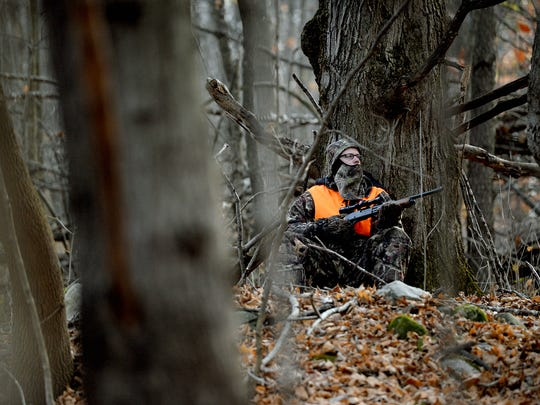 John Krohn sits up against a tree as he hunts for deer Thursday, Nov. 17, 2016 on a friend's land in Mason.
