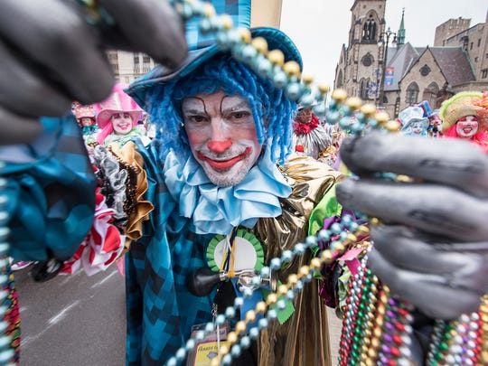 A member of the Distinguished Clown Corps hands out beads during the 90th annual America's Thanksgiving Parade along Woodward Avenue in Detroit Thursday, Nov. 24, 2016.