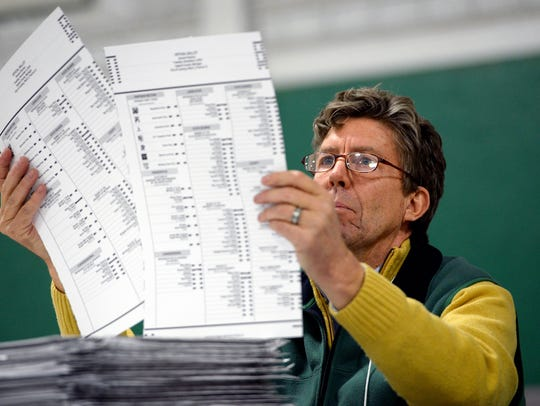 A recount worker with Ingham County looks over ballots